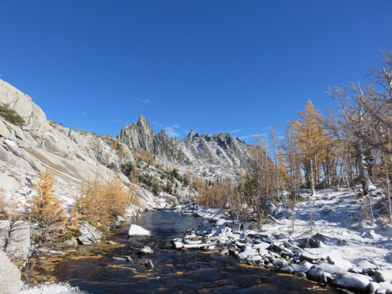 A mountain stream and granite peaks surrounded by yellow larch trees and snow covered ground.