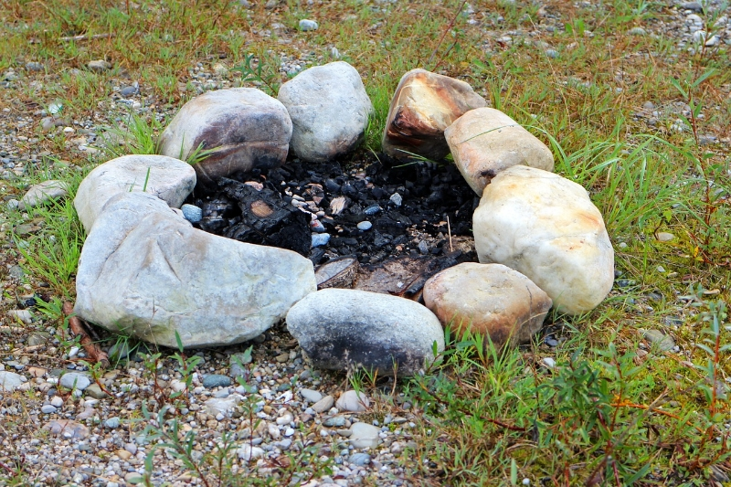 A stone fire ring in a field of grass with charred ground inside the fire ring.