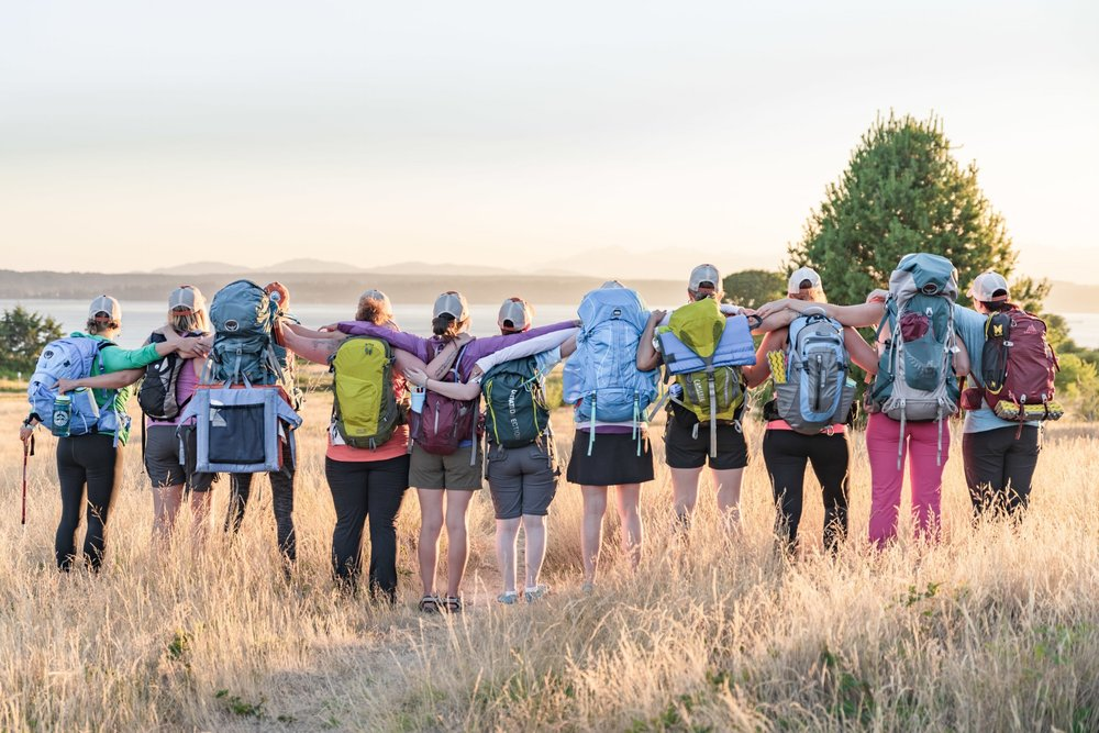 Eleven women with backpacks on facing away from the camera in a field of golden grasses.