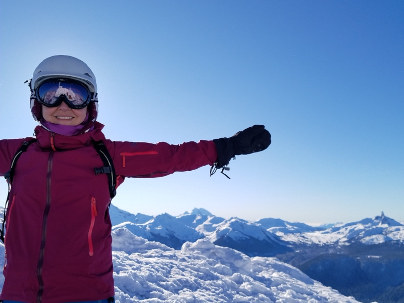 A smiling woman in a pink jacket with arms outstretched against a snowy mountain background and blue sky.