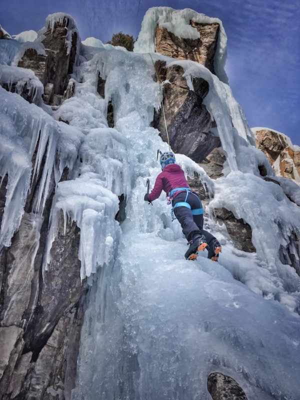 A woman in a pink jacket ice climbing.