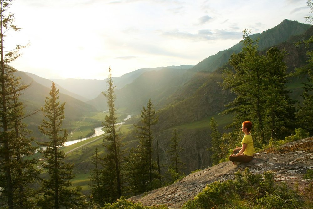 Woman sits on a rock in lotus pose overlooking a river valley