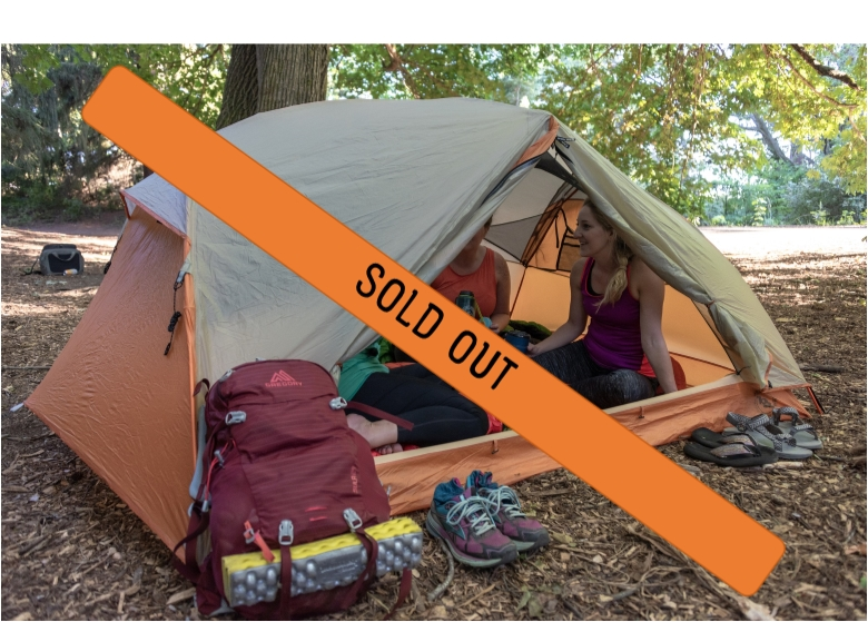 Outdoor dirt campsite with an orange tent surrounded by trees.