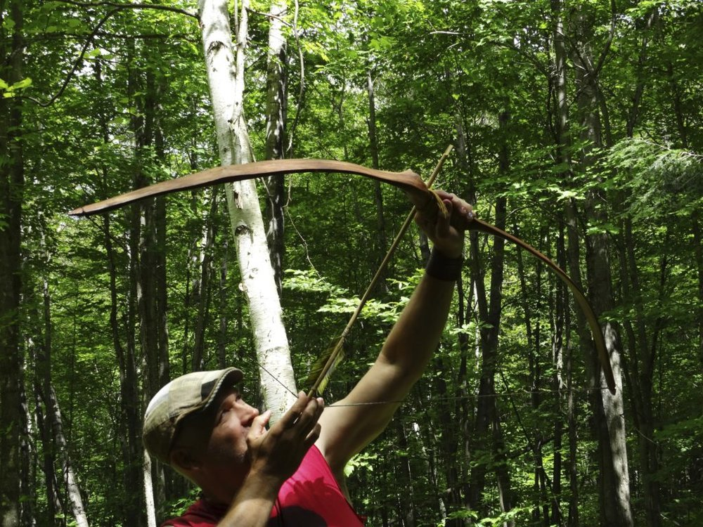 Stringing tree canopy with primitive homemade bow.