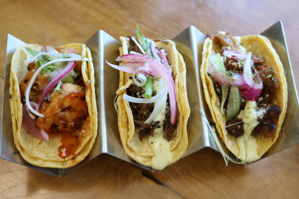 Tacos - Choice of three corn or flour tortillas, protein, Chinitos made sauce, cotija cheese and garnished with pickled red onions. Served with rice and beans