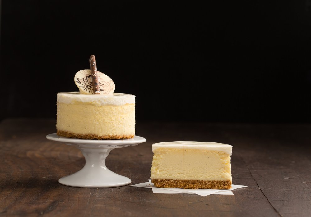 Vanilla Cheesecake - Cheesecake flavored with real Madagascar vanilla beans. The vanilla cheesecake sits on top of a graham cracker crust and is iced with a cream cheese icing. Finished with chocolate decorations.Contains: Wheat, Soy, Milk, Egg
