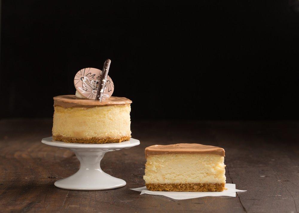 Dulce de Leche Cheesecake - A Dulce de Leche cheescake on a layer of graham craker crust with a white chocolate Dulce de Leche glaze.Contains: Wheat, Soy, Milk, Egg