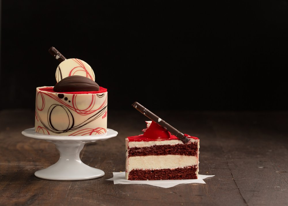 Red Velvet Cake - Red velvet cake layered with cream cheese icing. This pastry is nished with velvety cocoa butter and topped with chocolate decorations.Contains: Wheat, Soy, Milk, Egg