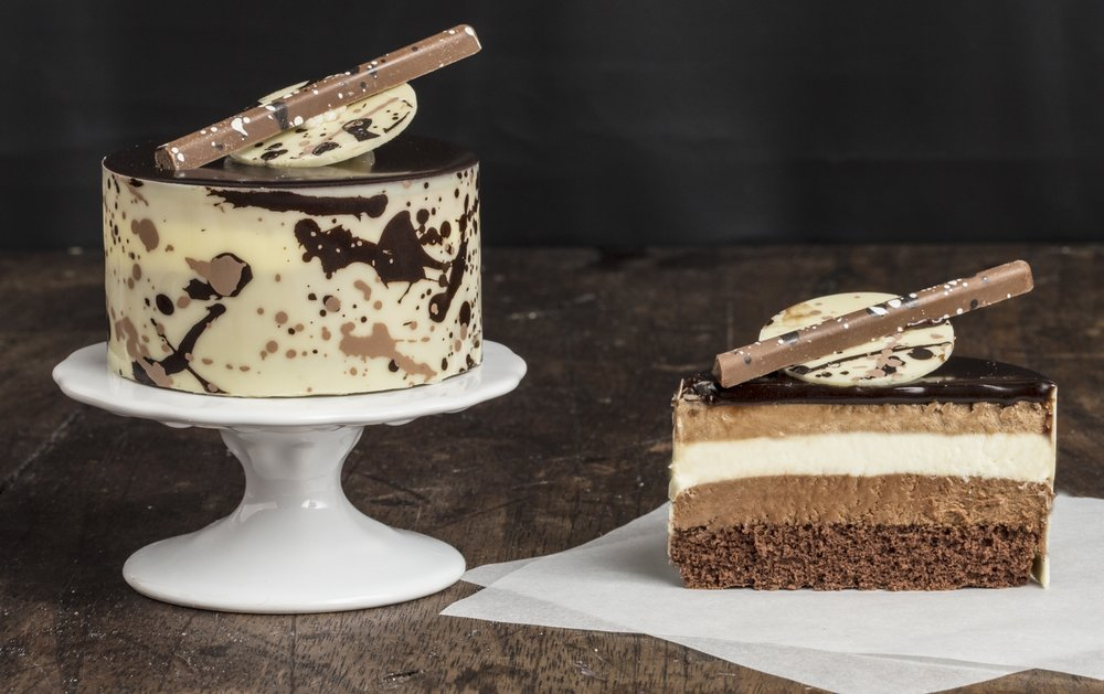 Gateau aux Trois Chocolat - Our Gâteau Aux Trois Chocolat has a chocolate genoise layered with white, milk and dark Bavarian Cream. Topped with chocolate ganache glaze and chocolate decorations. Contains: Wheat, Soy, Milk, Egg