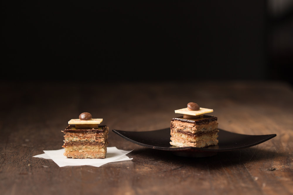 Mini L ' Opera - L'Opera cake is layers of almond cake soaked in co ee syrup, co ee butter cream, and dark chocolate ganache. Topped with dark chocolate icing and nished with chocolate decorations.Contains: Wheat, Soy, Milk, Egg, Almond