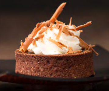 Chocolate Tartlette - Sweet chocolate tart shell lled with chocolate ganache and nished with whipped cream and chocolate shavings. Contains: Wheat, Soy, Milk, Egg