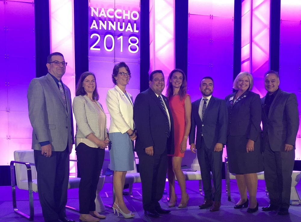 From left:  Kevin G. Sumner, MPH , President of NACCHO;  Catherine Patterson , MPP, Senior Program Officer, de Beaumont Foundation;  Colleen Bridger , MPH, PhD, Director, San Antonio Health District;  Andre Quintero , Mayor, El Monte, CA; Sarah Martin, PhD, MPP, MPH, Deputy Director, City of Kansas City, MO Health Department;  Bechara Choucair , MD, Chief Community Health Officer, Kaiser Permanente;  Lori Tremmel Freeman , Chief Executive Officer, NACCHO;  Umair Shah , MD, MPH, Former President, NACCHO