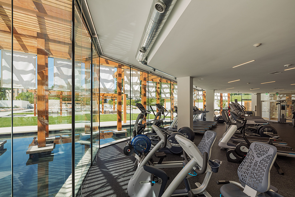 The fitness center overlooking the spacious pool area at Presidential City Apartments.