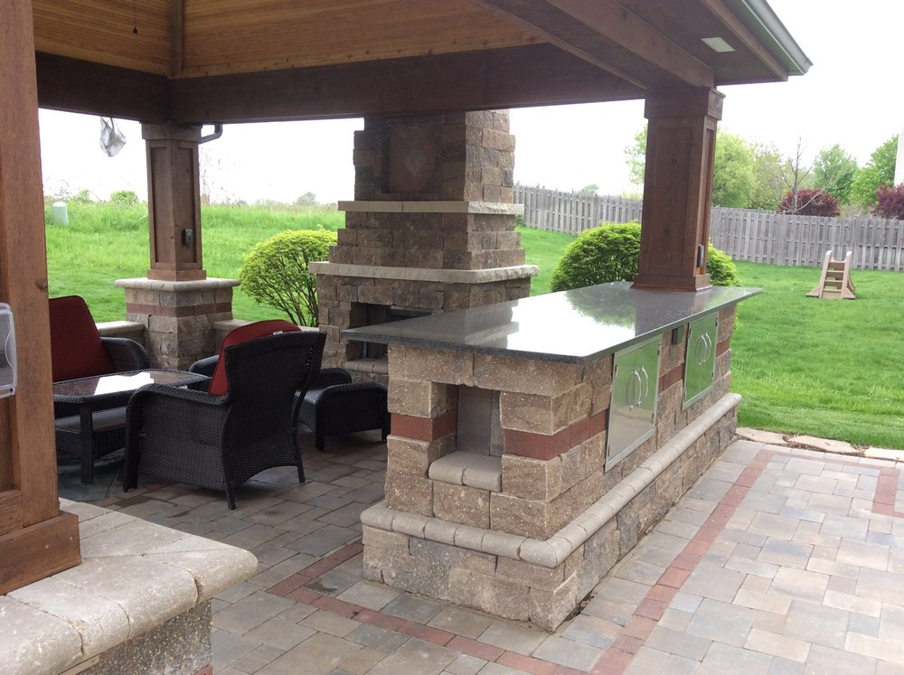 Brick paving patio that includes outdoor kitchen and outdoor fireplace in Elmhurst, IL