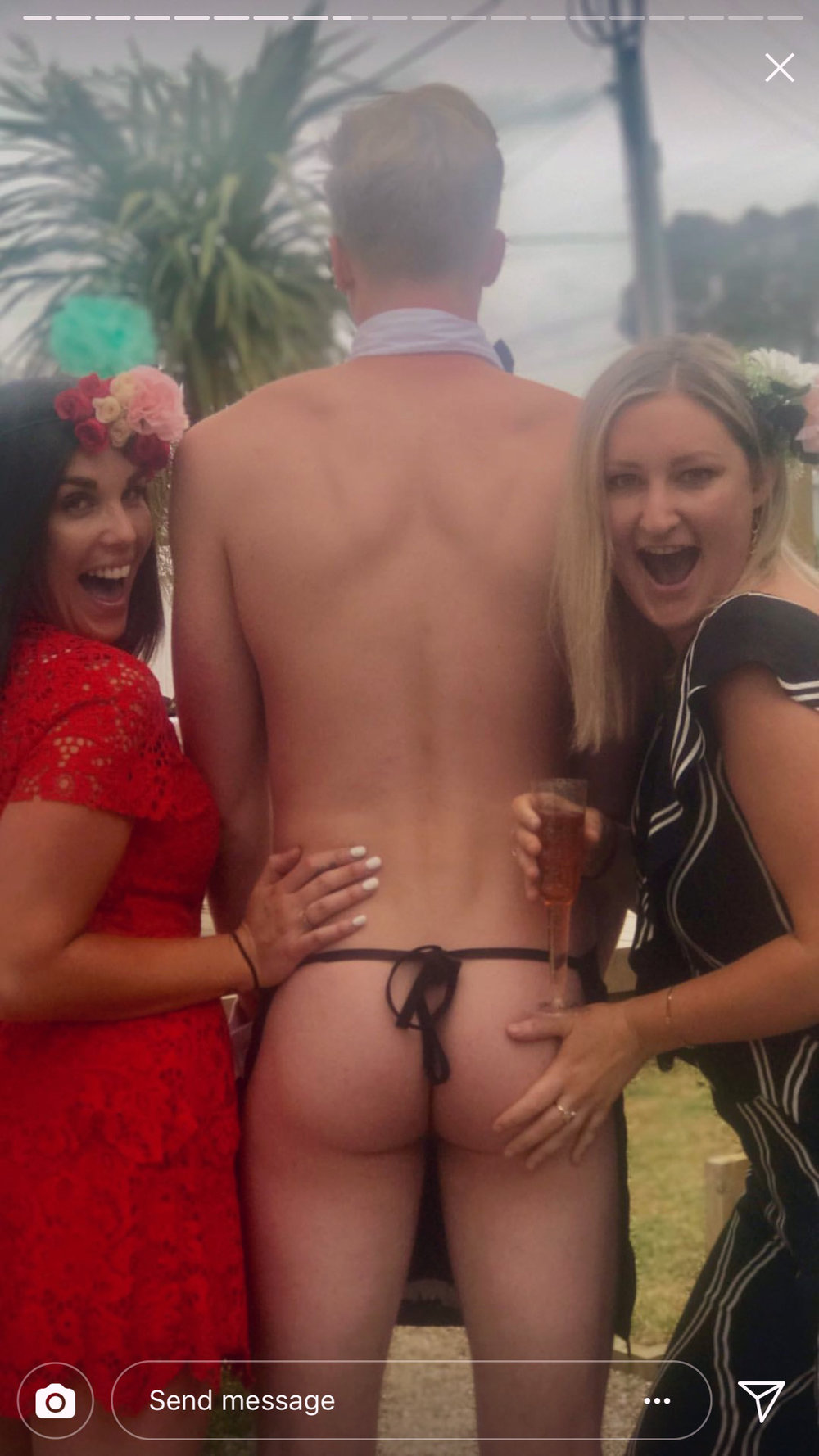 Bridesmaids pose with topless waiter's bare buns