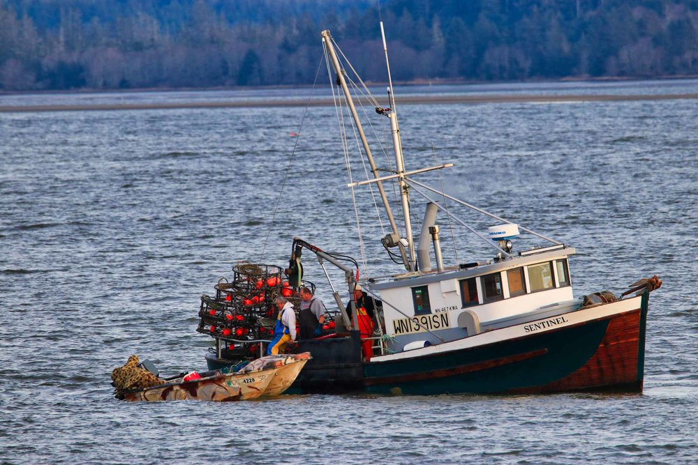 The crew of the F/V Sentinel stopping to help a local fisherman with some engine trouble.