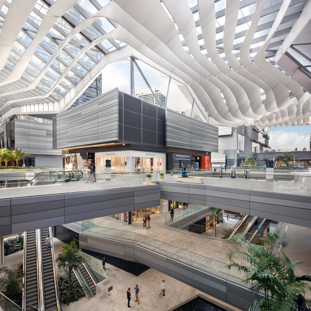 Winding through the development is the BCC Retail space, an open air mall covered by the climate ribbon, designed to move air through the building and keep it cool without the use of A/C