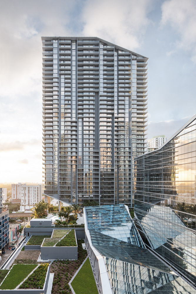 RISE at sunset, visible are the green roofing and climate ribbon which connects all of the towers in the development.