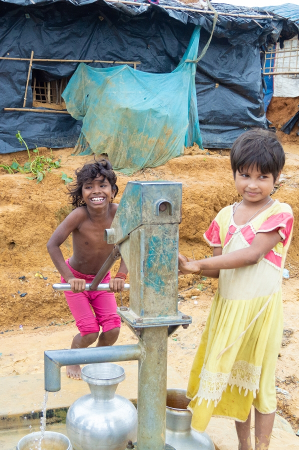 Two young survivors pump water for their families in the Bangladesh refugee camps. Photo by  Leif B. Kennedy , June 2018.