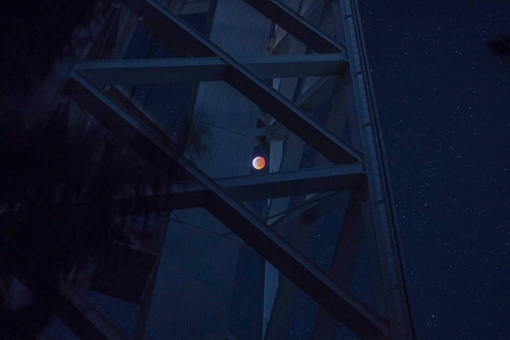 The moon passing exiting totality as seen through the supports of the historic 150' ft solar tower at Mt. Wilson Observatory.