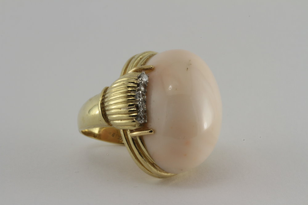 a large vintage angelskin coral in 18k gold with diamonds on either side