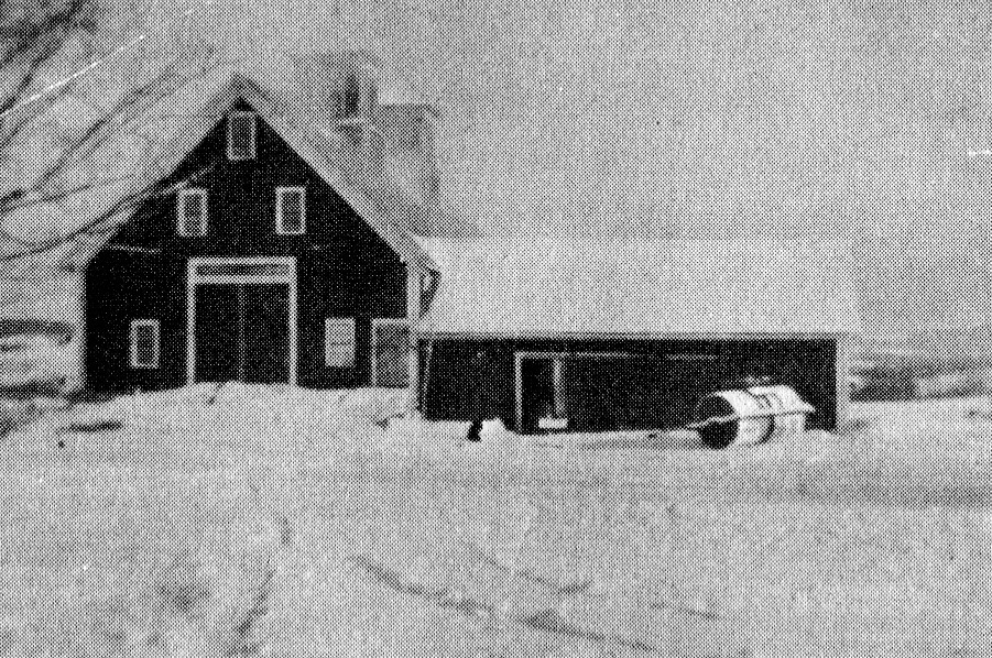 Barn winter scene with the Town Snow Roller seen in front.