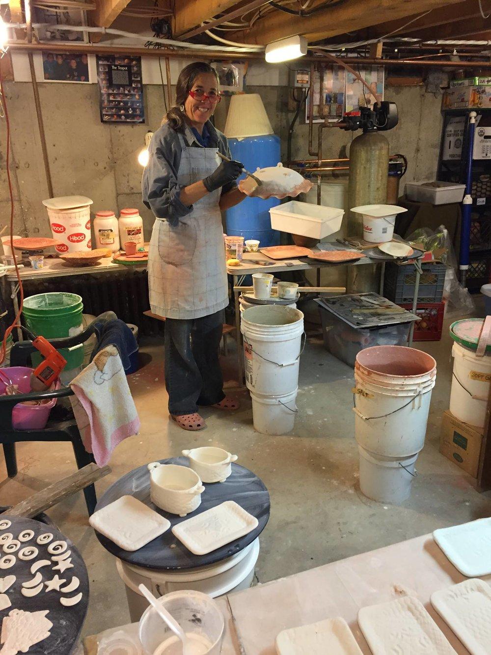 Jennifer in her ceramics studio applying glazes.
