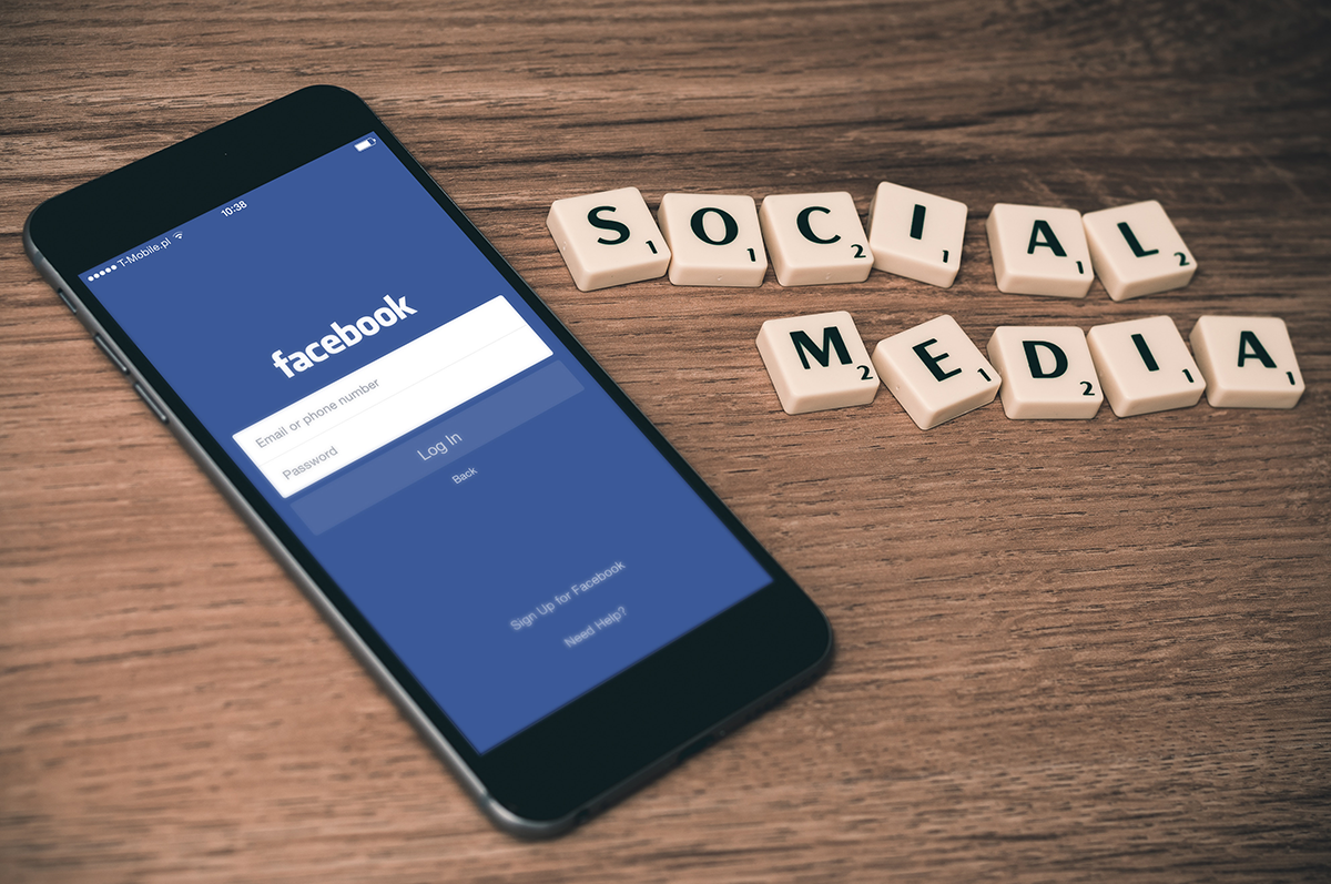 Social Media spelled in scrabble tiles and the facebook mobile app log-in page
