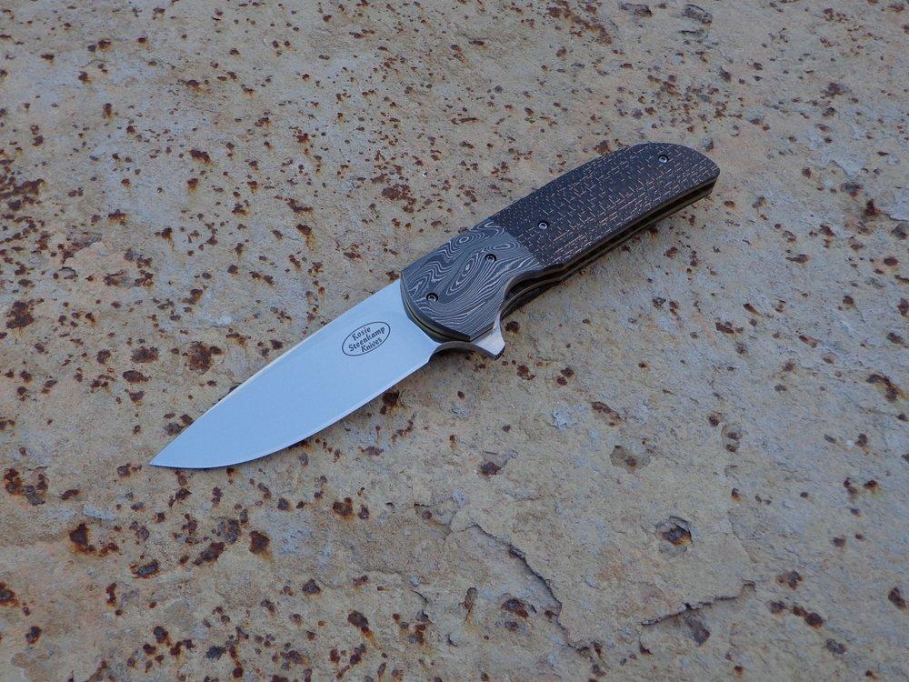 Knife: Majesty Flipper. Blade: Böhler N690 Stainless Steel. Bolsters: Alabama Damascus Steel. Handle scales: LS Carbon Fiber. Liners: Titanium, anodized golden. Pocket clip: Alabama Damascus Steel.