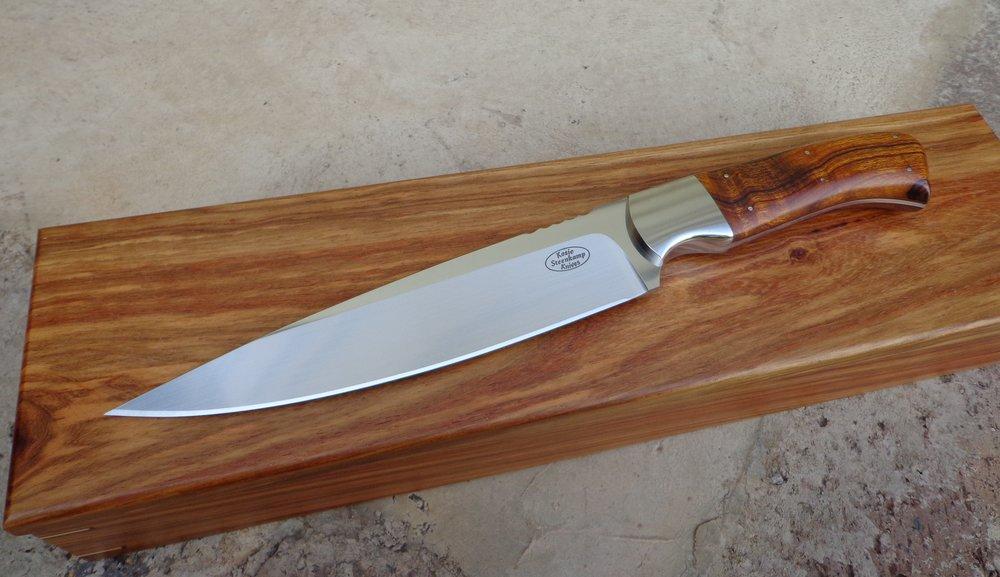Knife: Wedding Cake/Chef's Knife.  Blade: Böhler N690 Stainless Steel.  Coachwork: 304 (18/8) Stainless Steel.  Handle slabs: Arizona Desert Ironwood.