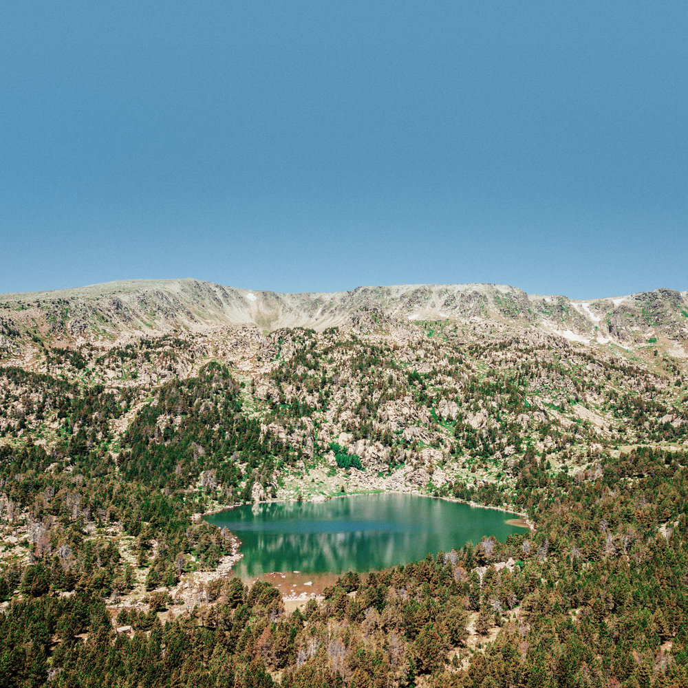 Lake Malniu  Lake Malniu is a glacial lake located 2250 metres above sea level. Located close to a mountain cabin and a forest track, it is one of the most popular lakes in the Eastern Pyrenees and a jumping off point for some of the best-known peaks in the region.