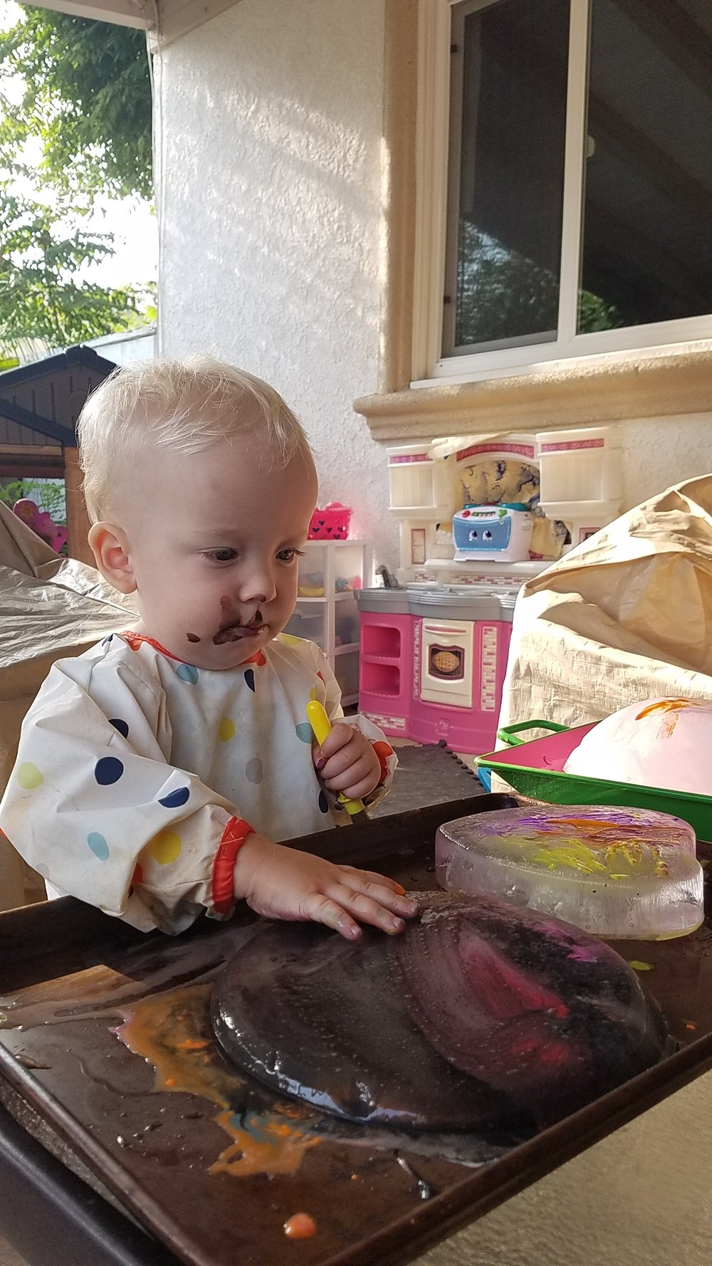 Using his hands to paint, while holding the paintbrush in his other hand.