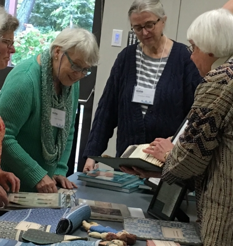 Authors, Norma Smayda and Gretchen White discussing BGH weavings with Claire Wanabo.