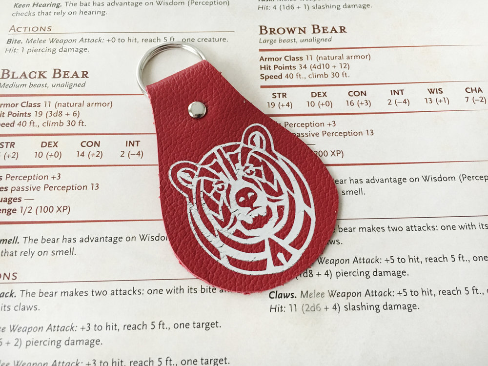 Small example of silver foil on crimson leather.