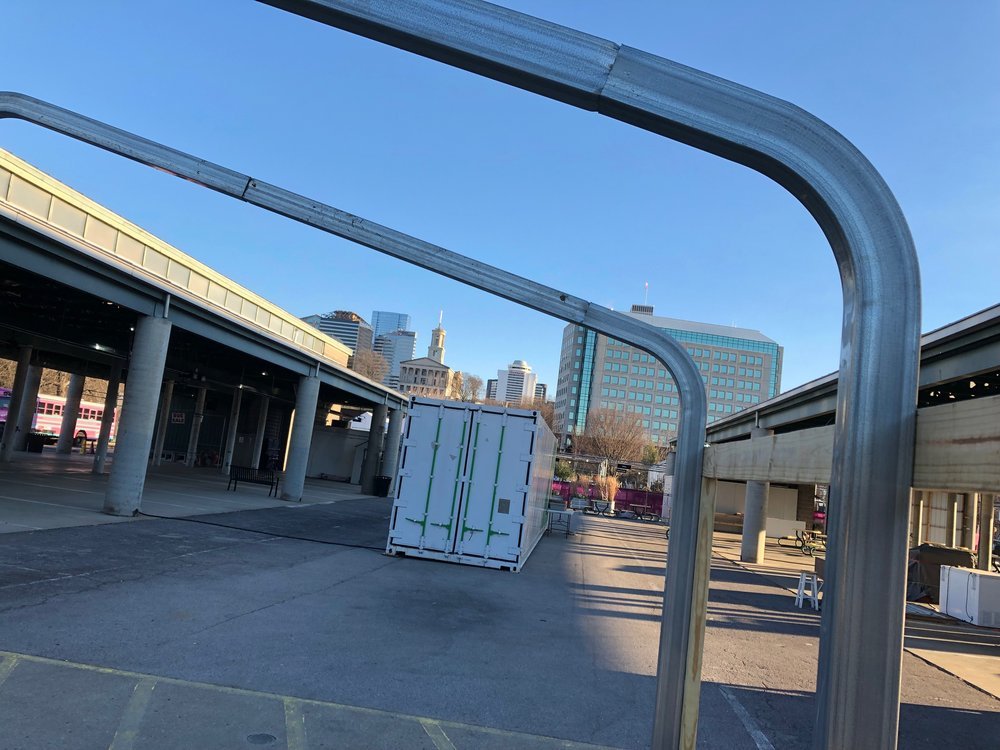 A shot of Rally House's container farm as seen through the framework for Bass Farm's greenhouse. Both are located between the Farm Sheds to the south of the Market House.