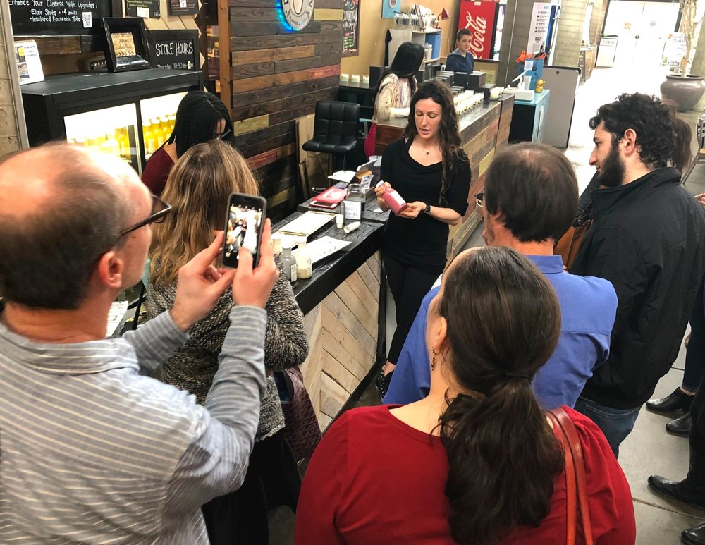 Jessica Goldberg, owner of The Fountain of Juice at the Nashville Farmers' Market, tells members of the California Almond Board about how she uses almonds while doling out samples.