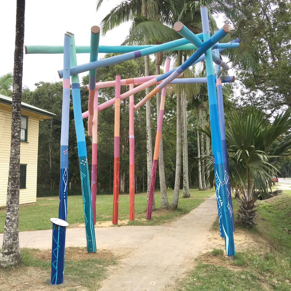 Enter Here I 2016  - Painted timber poles and hardware.Mullumbimby Sculpture Walk. Commissioned by Creative Mullumbimby Inc.This is a gateway sculpture and entrance to the proposed Mullum Sculpture Walk. It marks the beginning of the walk both geographically and in time at the commencement of a project that will continue indefinitely.