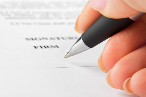 Hand with pen and contract - business background
