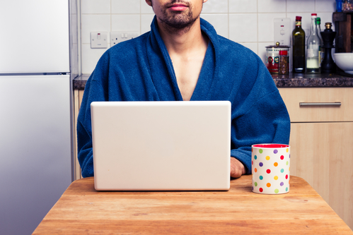 Man in robe working from home