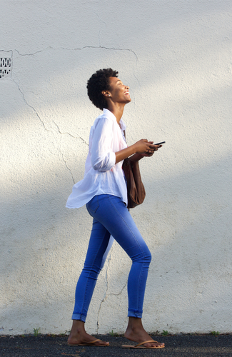 Full length side portrait of a smiling black woman walking on street with a mobile phone