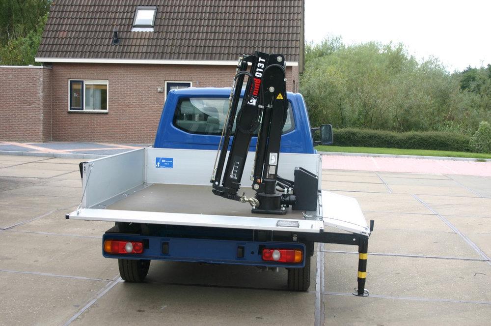 Achteraanzicht bedrijfswagen met open laadbak en laad en loskraan zijklep naar beneden steun op de grond.jpg