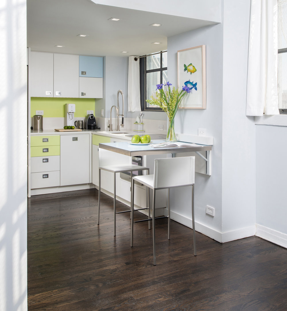 New York Apartment Renovation - Kitchen view 2  - Color choices of grass green and light blue and the abundant natural light streaming in from the large steel-frame windows create an overall sense of freshness and lightness.