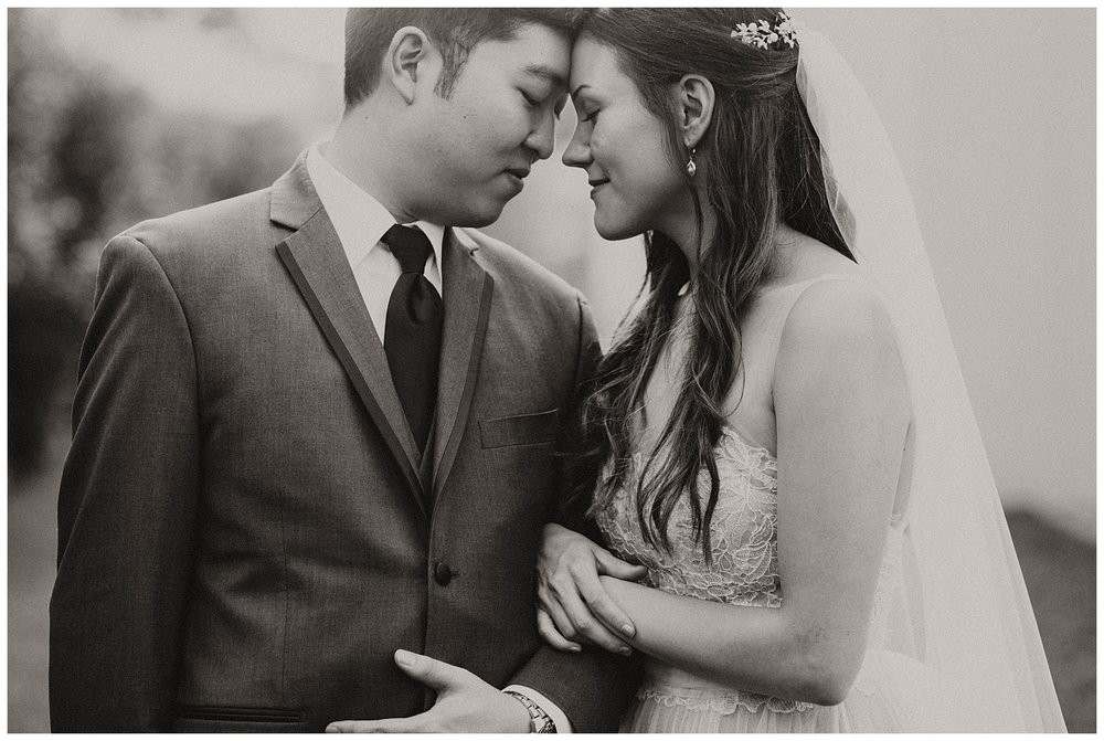B&W image of bride and groom. Sweet moment with their foreheads together.