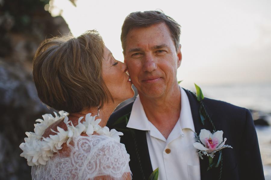 groom kisses maui wedding