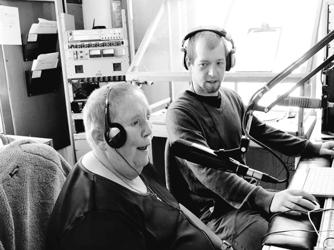 Black and white photo of a man and a women wearing headphones and sitting in a broadcasting studio.