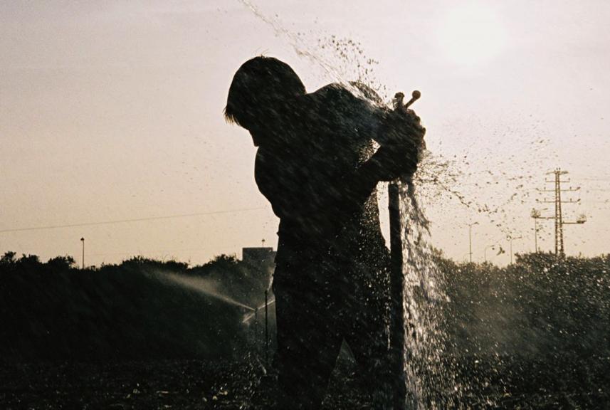 Un homme répare un combiné d'arrosage dans un camp de la vallée de Hefer (Photo d'illustration : Gili Yaari /Flash90)