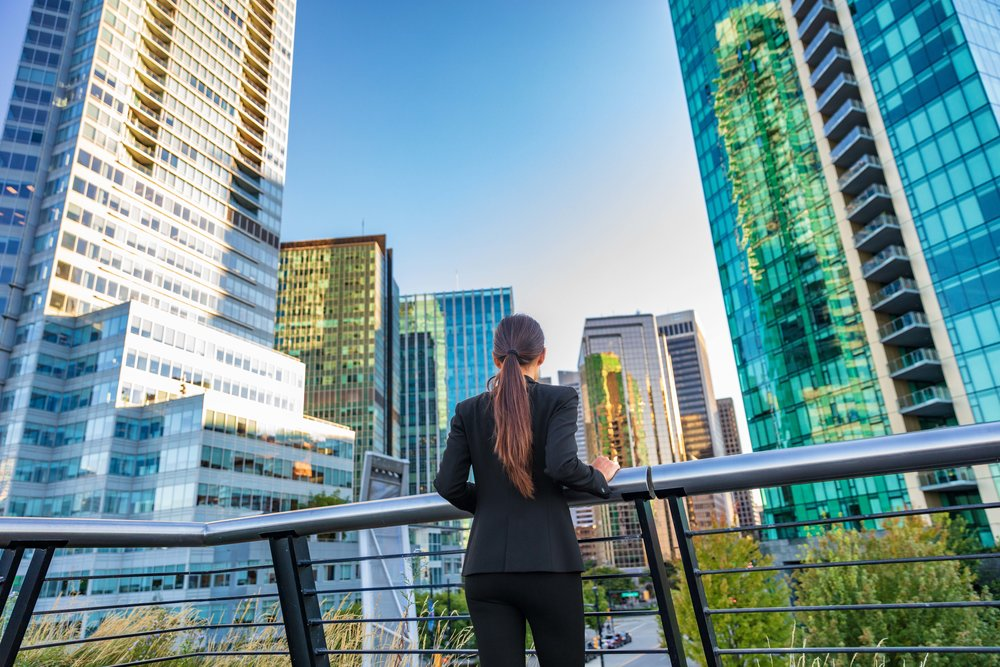 Business woman in city center looking at view of skyline skyscra