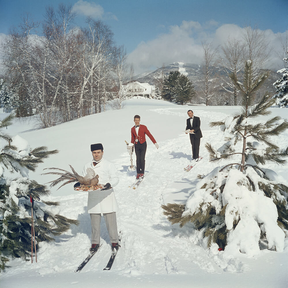 Three skiing waiters on a ski slope, with the man in the foreground carrying a bird on a tray, the second man carring a wine in an ice bucket and the third carrying a menu, 1962. (Photo by Slim Aarons/Getty Images)