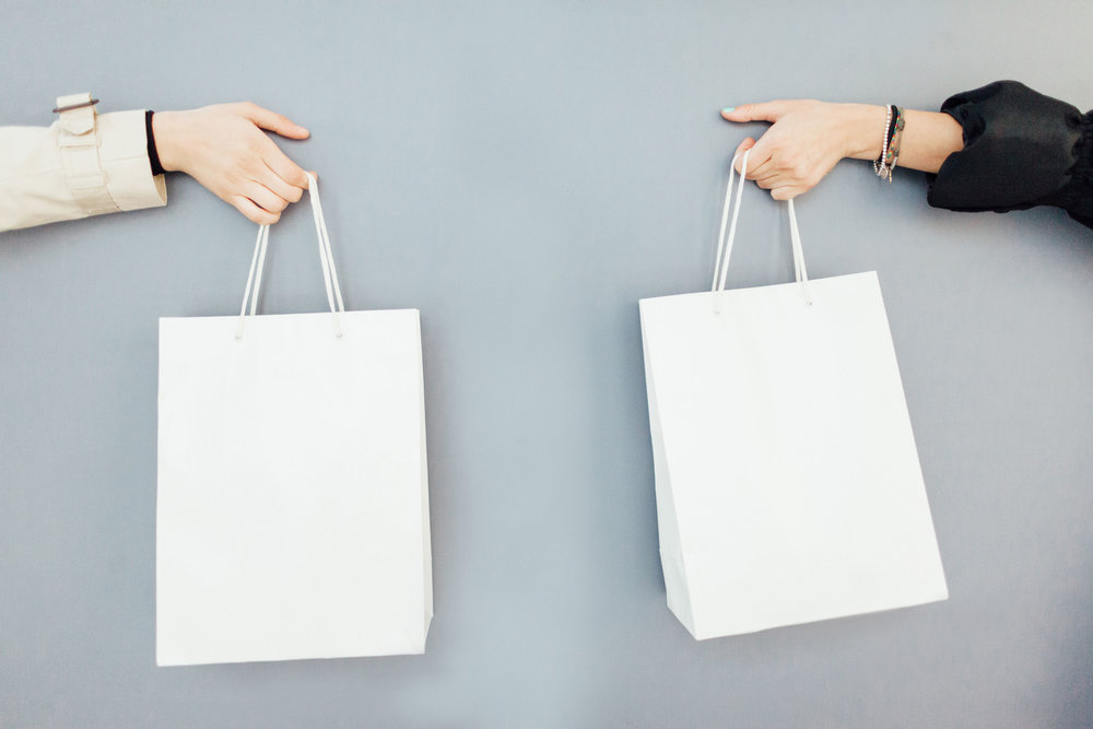 Two Female Hands Holding Shopping Bags