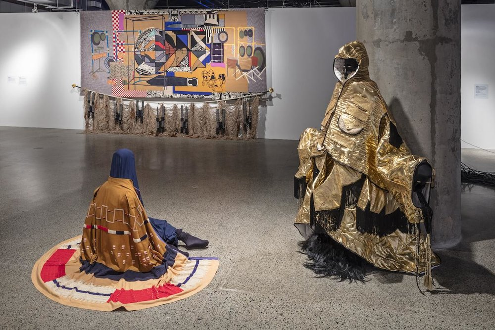 Nep Sidhu's No Pigs in Paradise garments and his tapestry, The Sound Sculpture Forms & Knowledge Transfers of Kahil El'Zabar (When My Drums Come Knocking, They Watch Series). Image by Toni Hafkenscheid